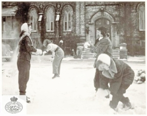 students-having-a-snowball-fighton-the-front-lawn-of-alma-college