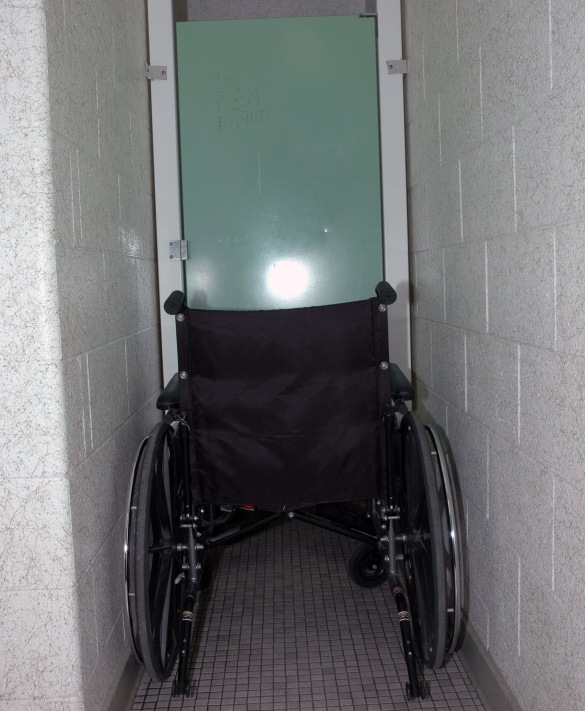 Even if you were able to grapple a wheelchair through the main door, the cubicle itself will halt your progress.